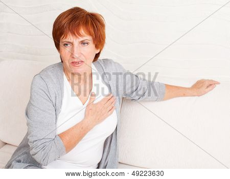 Cardiac pain. Mature woman holds her heart