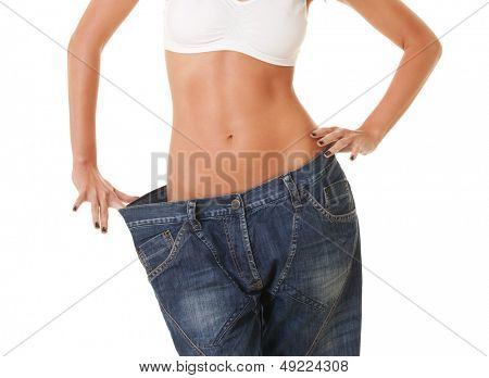 woman shows her weight loss by wearing an old jeans, isolated on white background