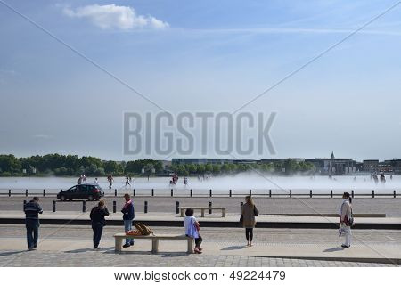 BORDEAUX, FRANCE - JUNE 27: People walk on the water mirror on the Place de la Bourse in Bordeaux, France on June 27, 2013. Opened in 2006, the water mirror is the largest in the world with 3450 sq. m