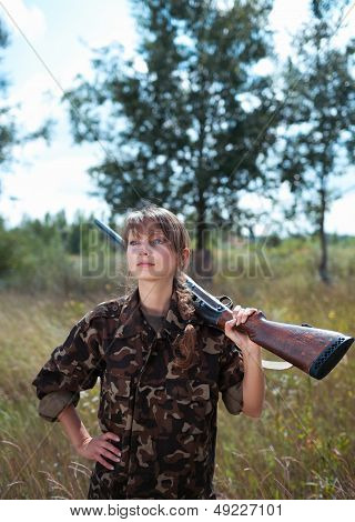 Young Beautiful Girl With A Shotgun In An Outdoo