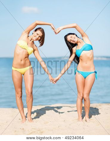summer holidays and vacation - girls in bikinis making heart shape with hands on the beach