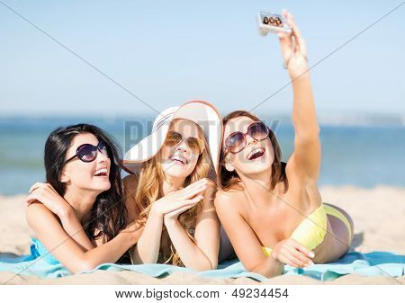 summer holidays, vacation and beach concept - girls in bikinis taking self photo on the beach
