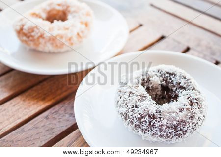 Delicious Chocolate And Vanilla Coconut Donuts On Wooden Table