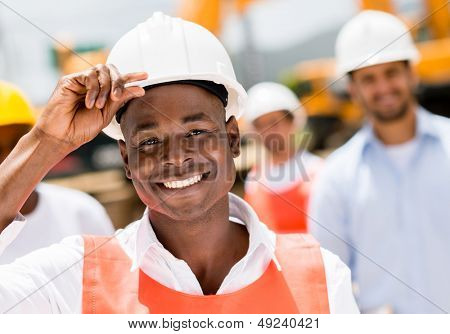 Happy construction worker at a building site wearing a helmet