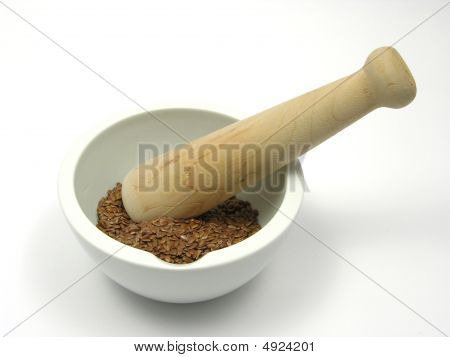 Pestling Brown Flaxseed In A Bowl Of Chinaware