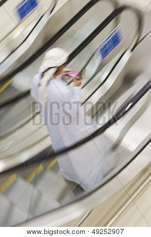 Dubai UAE A man traditionally dressed in a dishdash and gutra white robe and headdress.