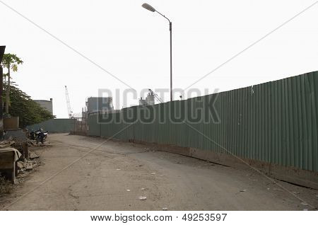Dirt Road Along Enclosed Corrugated Steel Fence