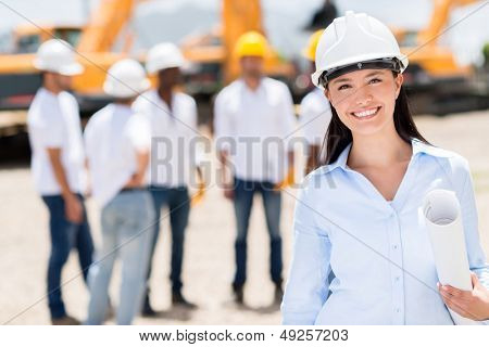 Female architect at a construction site looking happy