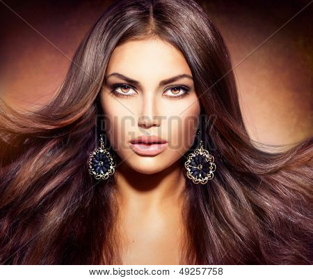 Glamour Beautiful Woman with Beauty Brown Hair. Blowing Long and Healthy Hair. Professional Make up. Fashion Earrings