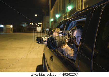 Fotógrafos profissionais com teleobjetiva no carro