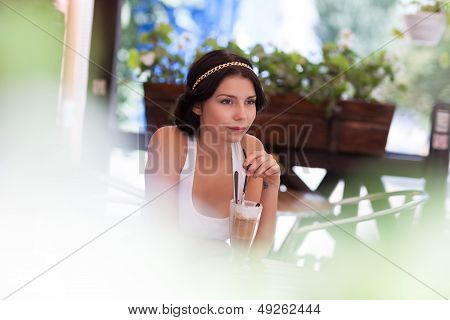 Young Girl Drinking Cappuccino In A Cafe