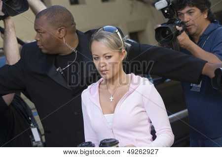 Closeup of a female celebrity and bodyguard surrounded by paparazzi