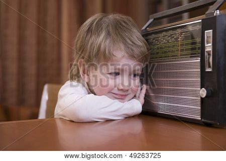 Closeup of a cute boy listening to retro radio at home