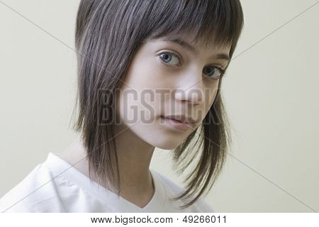 Closeup portrait of a serious young girl with brown hair against colored background