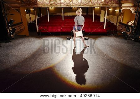 Full length of a young woman with script rehearsing on stage