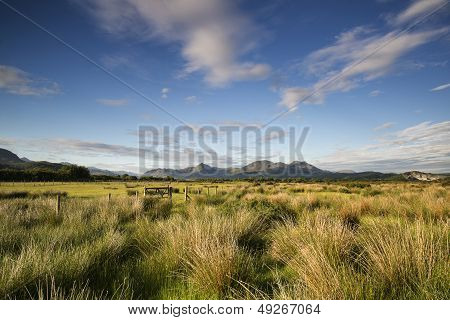 View From Porthmadog Cob Towards Snowdonia Mountains Landscape During Summer Evening