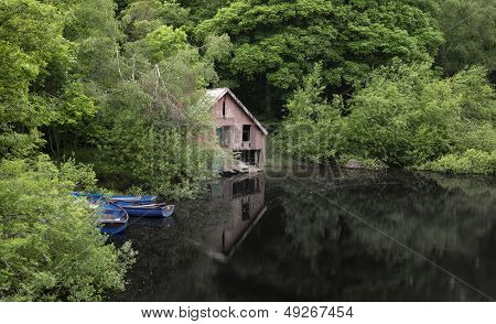 Derelict Old Retro Boathouse And Rowing Boats Hidden In Forest Lake In Summer