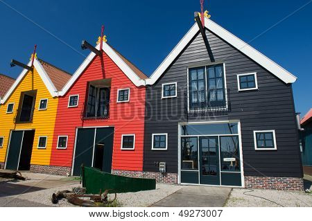 Colorful wooden warehouses in Dutch village Zoutkamp wilt part of fishermans boat in front