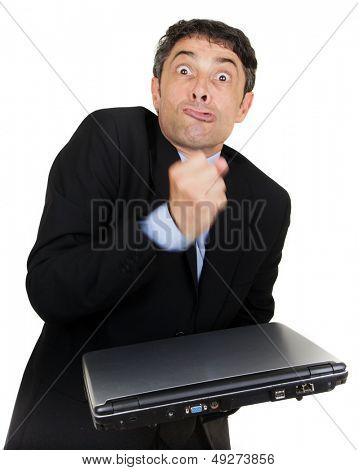 Exasperated man making a fist over his closed laptop computer which he is holding i his hand while grimacing at the camera, isolated on white