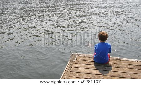 a young boy on a dock at the water's edge