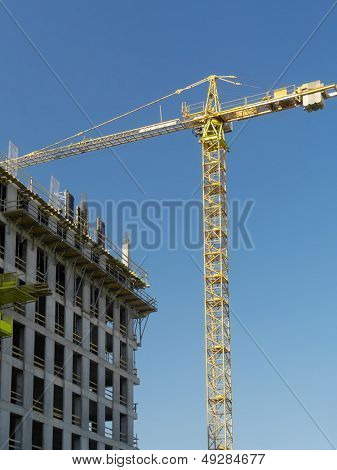 Generic highrise building under construction and jib crane over clear blue sky