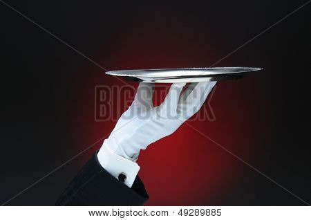 Closeup of a waiter's hand holding a silver serving tray in his fingertips over a light ot dark red background. Only the man's hand and arm are visible. He is wearing a tuxedo and formal white gloves.