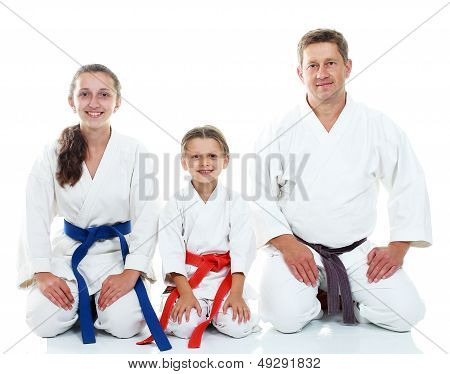 Dad with two daughters sitting in a ritual pose Karate