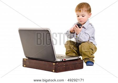 Cute small boy dials on a mobile phone while sitting next to laptop