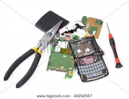 Broken cell phone in pieces with tools