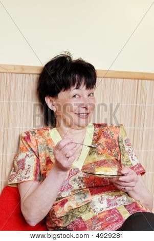 Senior Woman Eating Cake