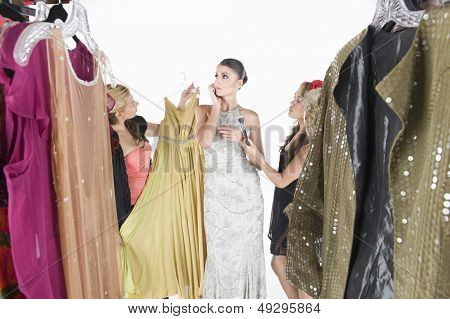 Contemplative fashion model ignoring wardrobe assistants against white background