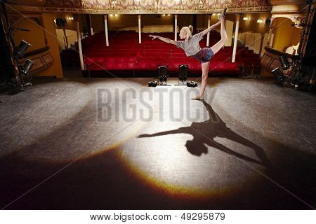 Full length side view of a young woman stretching on stage