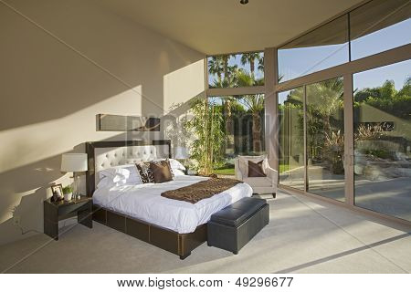 View of a spacious sunlit bedroom with porch view