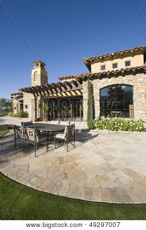 Paved dining area in front of modern house against clear blue sky