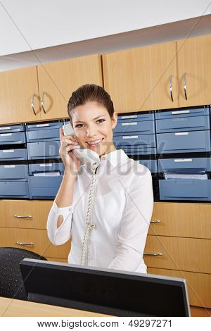 Young receptionist in a hospital taking a phone call