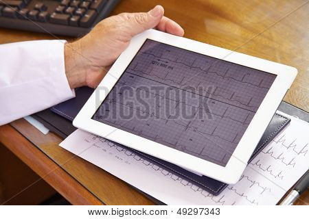 Doctor looking at ECG on a tablet computer in his office