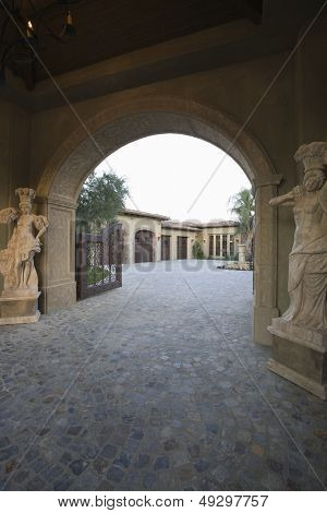 Paved driveway with arched entrance to modern house