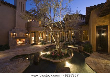 Paved courtyard with pond in lit house against clear sky