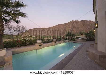 Paved poolside area of home against mountain and clear sky