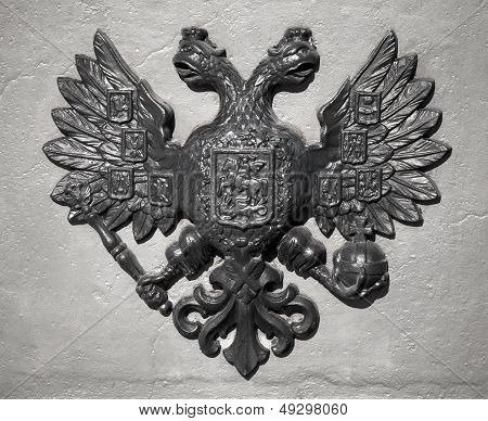 Double Eagle - Emblem Of Russia. Ancient Black Bas-relief On Gray Vintage Wall