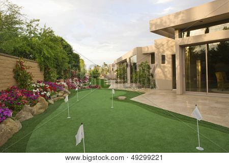 View of mini golf course in garden by luxury house