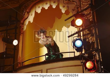 Low angle view of a cheerful young woman in theatre box