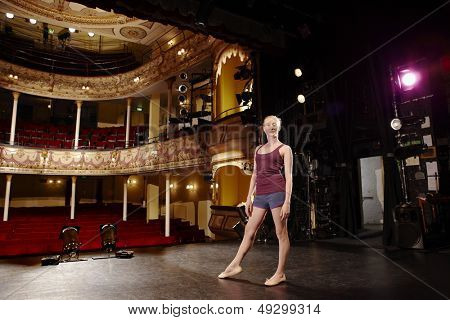 Full length portrait of a confident young ballet dancer on stage