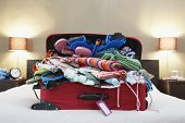 image of bulge  - Open suitcase on bed - JPG
