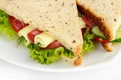 stock photo of salami  - Tasty sandwiches with salami sausage and vegetables on white plate - JPG