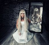 picture of creeping  - Young beautiful blond woman sitting on wooden floor in old dark room with big knife in mirror reflection - JPG