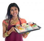 Happy Traditional Indian woman in sari baking bread and cupcakes, wearing apron holding tray isolate