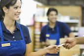 stock photo of supermarket  - Closeup of a hand giving female employee loyalty card in supermarket - JPG