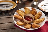 stock photo of pasteis  - Pastel a Brazilian snack with a bar in the background - JPG