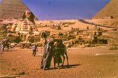 GIZA, EGYPT, CIRCA SIXTIES - vintage photo of female tourist with a camel driver, Giza, Egypt circa